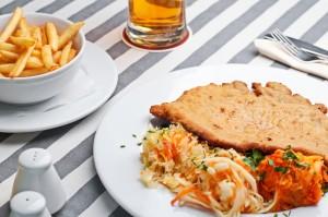 Podstawowe danie mięsne w naszym menu - Schabowy XL z frytkami i zestawem surówek najlepiej smakuje z zimnym piwem.