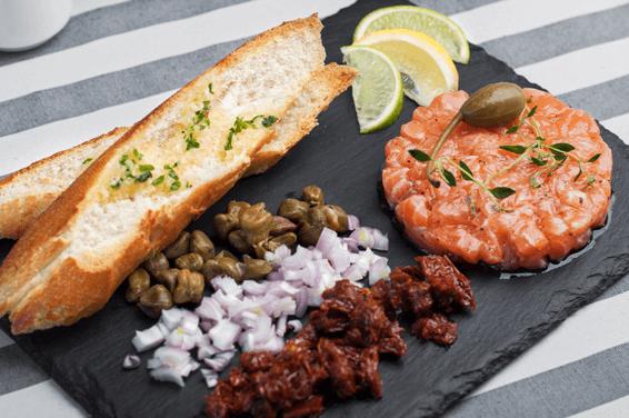 Tatar z łososia podawany z szalotką, kaparami, pomidorem suszonym