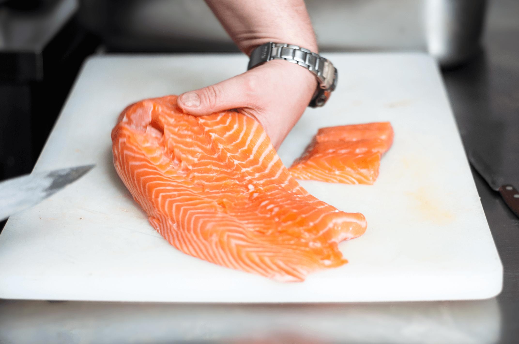 Kucharz starannie oporządza łososia, który po przygotowaniu trafi na restauracyjny strół